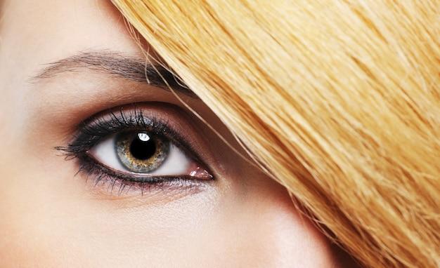 Zbliżenie kobieta oko z kreatywnym makijażem i fryzurą