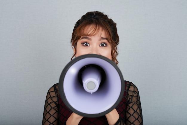 Zbliżenie kobieta patrzeje kamerę przeciw szarość z głośnikiem