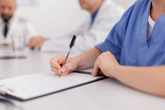 Zbliżenie: kobieta pielęgniarka ręce pisząc leczenie choroby w schowku, pracując w opiece medycznej, siedząc przy biurku w sali konferencyjnej