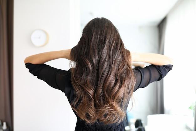 Zbliżenie: kobieta po wizycie u fryzjera. długie loki brunetki osoby płci żeńskiej. fryzura na wakacje lub na co dzień. koncepcja salon kosmetyczny i fryzurę