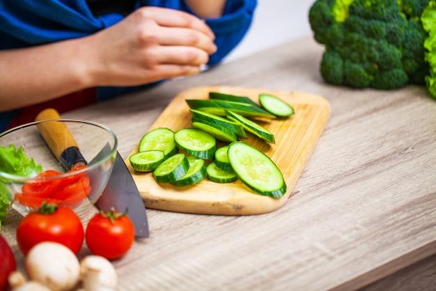 Zbliżenie kobieta pokrajać ogórek dla diety sałatki