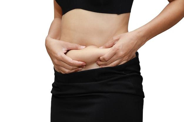 Zbliżenie kobieta pomiaru tłuszczu z brzucha z rękami na białym tle i biały