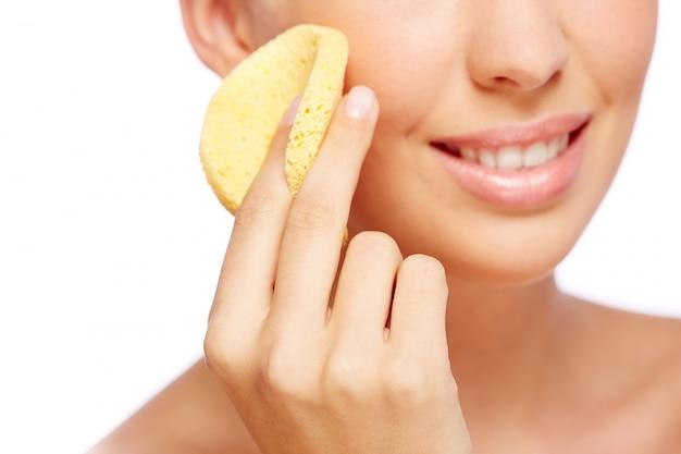 Zbliżenie kobieta przy użyciu gąbki na jej twarzy
