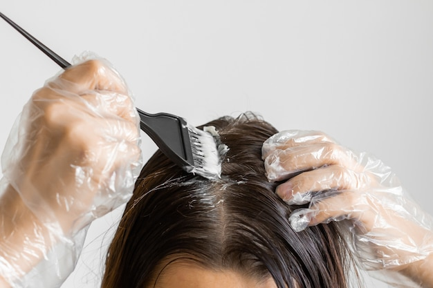 Zbliżenie kobieta ręce farbowanie włosów za pomocą czarnego pędzla. kolorystyka białych włosów w domu.
