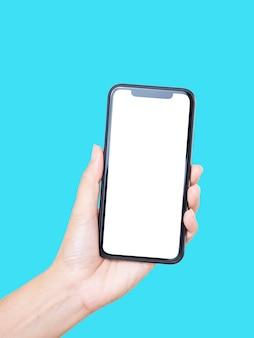 Zbliżenie: kobieta ręki trzymającej smartfon z pustym ekranem, makiety na niebieskim tle