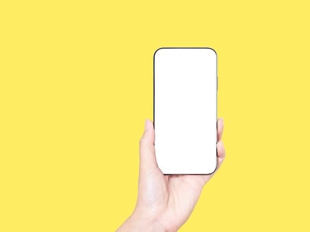 Zbliżenie: kobieta ręki trzymającej smartfon z pustym ekranem, makiety na żółtym tle