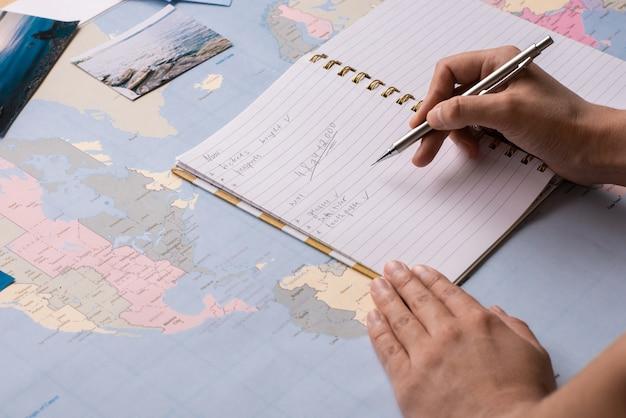Zbliżenie: kobieta sprawdzająca listę w notatniku podczas przygotowań do podróży