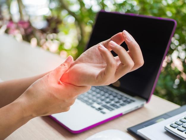 Zbliżenie kobieta trzyma jej nadgarstku ból od używać komputer. zespół biurowy.