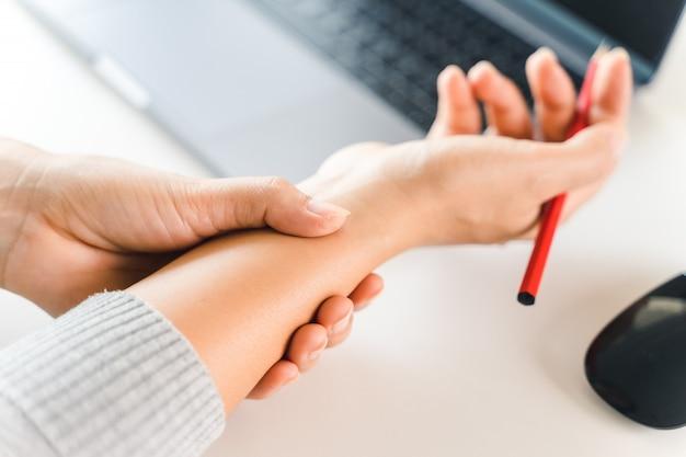 Zbliżenie kobieta trzyma jej nadgarstku ból od używania komputerowego długiego czasu. koncepcja zespołu office.