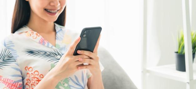 Zbliżenie: kobieta trzyma smartfon i korzysta z internetu społecznego