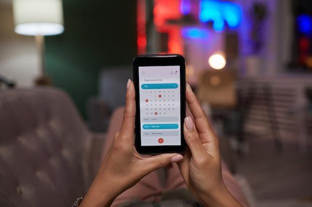 Zbliżenie: kobieta trzyma telefon komórkowy i przy użyciu kalendarza online w domu