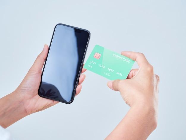 Zbliżenie: kobieta trzyma telefon komórkowy, pusty ekran i kredytową kartę bankową na szarym tle