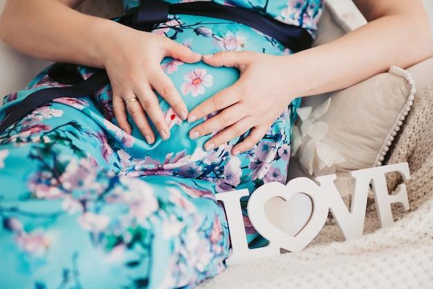 Zbliżenie: kobieta trzymając się za ręce na brzuchu.
