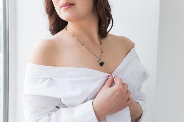 Zbliżenie: kobieta ubrana w złoty naszyjnik. biżuteria, biżuteria i dodatki.