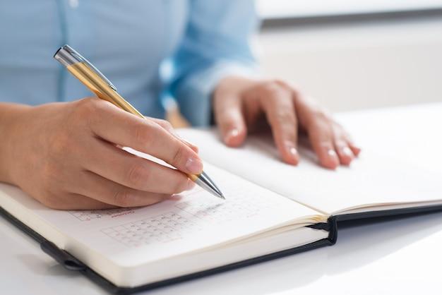 Zbliżenie kobieta używa dzienniczek i harmonogramować