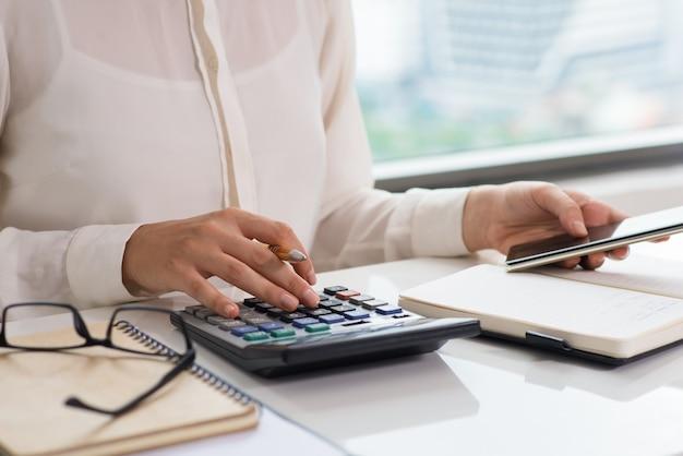 Zbliżenie kobieta używa kalkulatora i mądrze telefon
