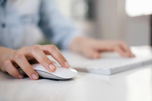 Zbliżenie kobieta używa komputerowej myszy z komputerową klawiaturą