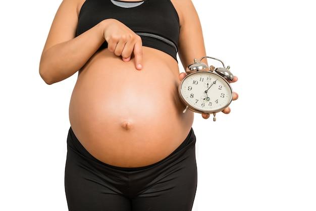 Zbliżenie: kobieta w ciąży, trzymając budzik, spodziewa się dziecka