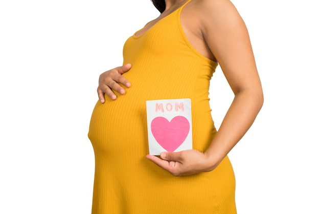 Zbliżenie: kobieta w ciąży, trzymając kartkę z życzeniami