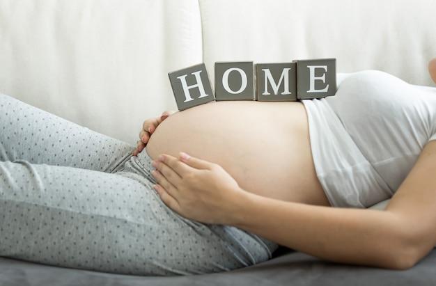 Zbliżenie kobieta w ciąży, trzymając słowo home na brzuch