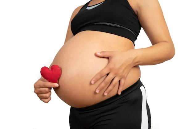 Zbliżenie: kobieta w ciąży, trzymając znak serca na brzuchu