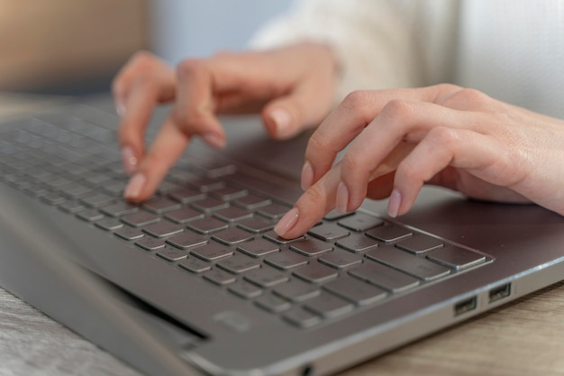 Zbliżenie: kobieta wpisując na laptopie