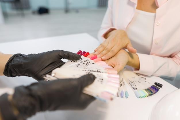 Zbliżenie: kobieta wybiera kolor lakier do paznokci na paznokcie