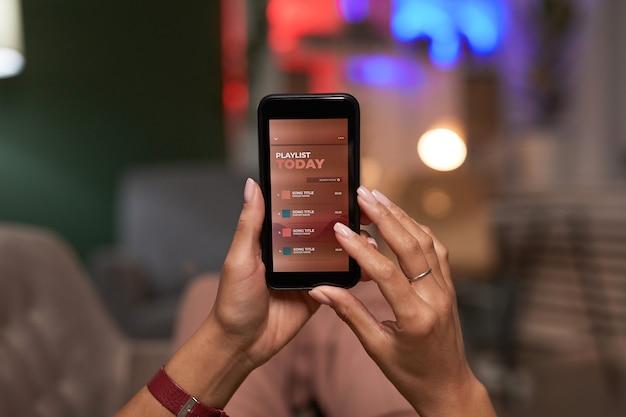 Zbliżenie: kobieta z telefonem komórkowym, słuchanie muzyki online