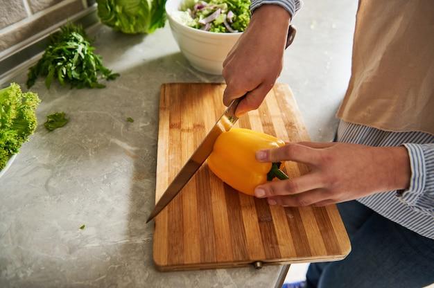 Zbliżenie kobiety cięcia papryki do przygotowania sałatki. zbliżenie