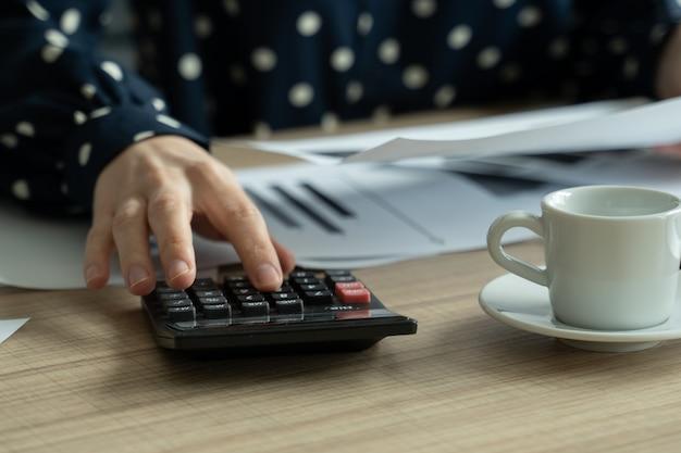 Zbliżenie kobiety, która planuje budżet za pomocą kalkulatora i laptopa, czytając dokumenty siedząc przy biurku