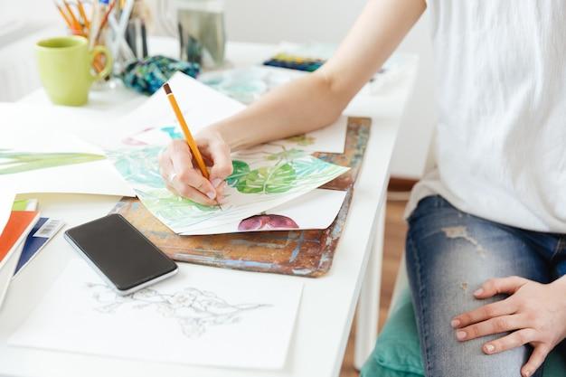 Zbliżenie kobiety malarz rysujący w pracowni artystycznej