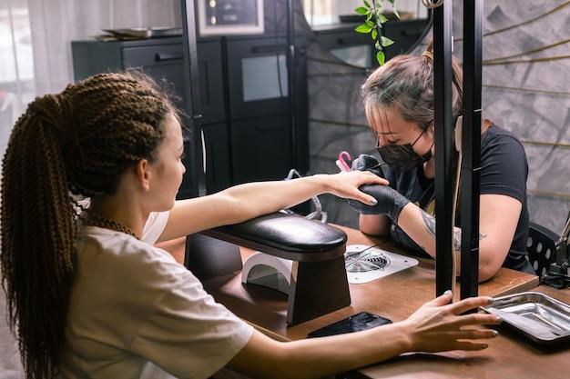 Zbliżenie kobiety manikiurzystki usuwa żelowy lakier szelakowy z paznokci klienta za pomocą maszyny do manicure