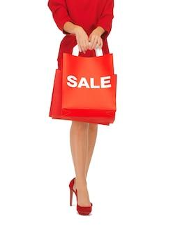 Zbliżenie kobiety na szpilkach trzymającej torbę na zakupy