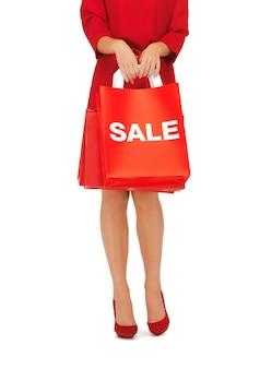 Zbliżenie kobiety na szpilkach trzymającej torby na zakupy