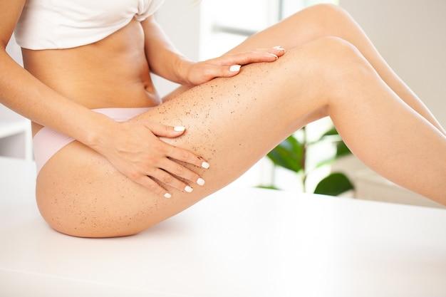 Zbliżenie kobiety nogi z peelingiem do pakowania antycellulitowy kawy.
