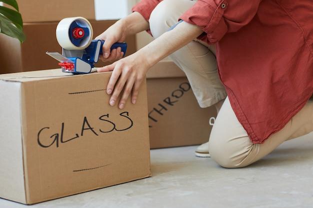 Zbliżenie kobiety pakowania podpisanych pudełek taśmą klejącą podczas przeprowadzki