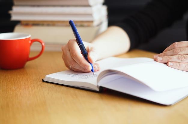 Zbliżenie kobiety pracującej lub studiującej w domu przy filiżance czerwonej kawy w pobliżu