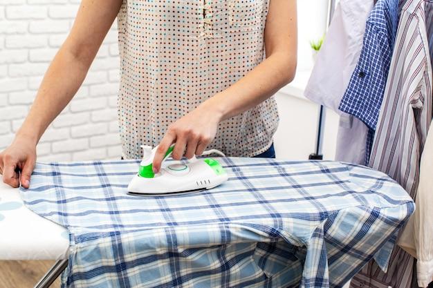 Zbliżenie kobiety prasowanie odziewa na prasowanie desce