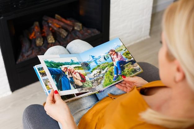 Zbliżenie kobiety przeglądającej album ze zdjęciami, fotoksiążka
