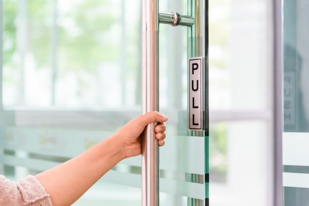 Zbliżenie kobiety ręka otwiera drzwiową gałeczkę
