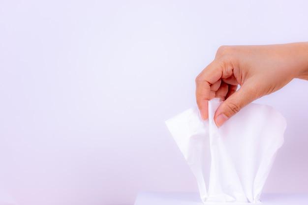 Zbliżenie kobiety ręka podnosi białą bibułkę od tkanki pudełka.