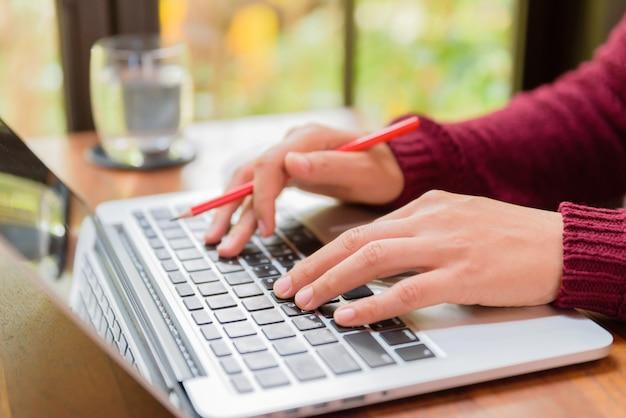 Zbliżenie kobiety ręka pracuje na jej laptopie.