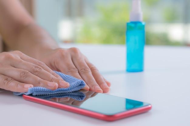 Zbliżenie kobiety ręki używać alkoholową kiść czyścić mądrze telefon, przeciw chorobie coronavirus.