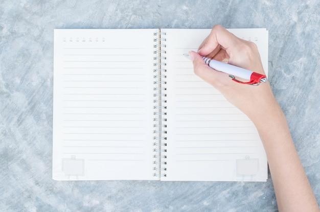 Zbliżenie kobiety ręki writing na nutowej książce w odgórnym widoku