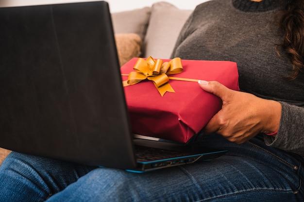 Zbliżenie kobiety rozmawia z przyjaciółmi na laptopie i pokazuje im czerwone pudełko