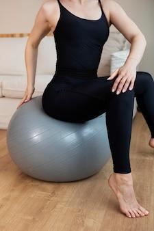 Zbliżenie kobiety siedzącej na piłce gimnastycznej