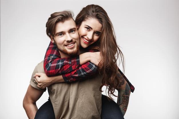 Zbliżenie kobiety siedzącej na plecach mężczyzny, patrząc szczęśliwy.