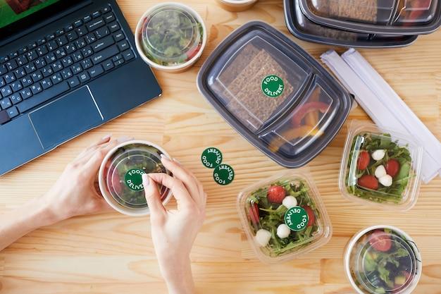 Zbliżenie kobiety siedzącej przy drewnianym stole i realizującej dostawę online, która umieszcza naklejki na pudełkach
