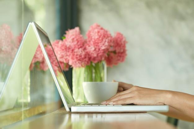 Zbliżenie kobiety siedzącej w domowym biurze za pomocą laptopa