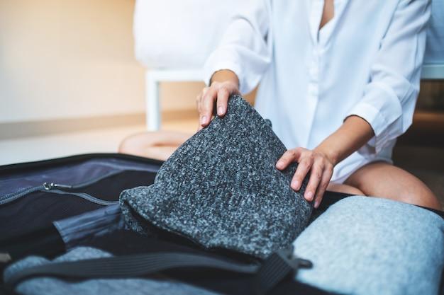Zbliżenie kobiety składanie ubrania i pakowanie bagażu na wycieczkę